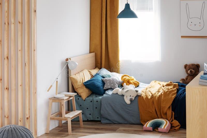 Stilvoller Schlafzimmerentwurf des blaues und orange Kindes in der hellen Wohnung stockbild