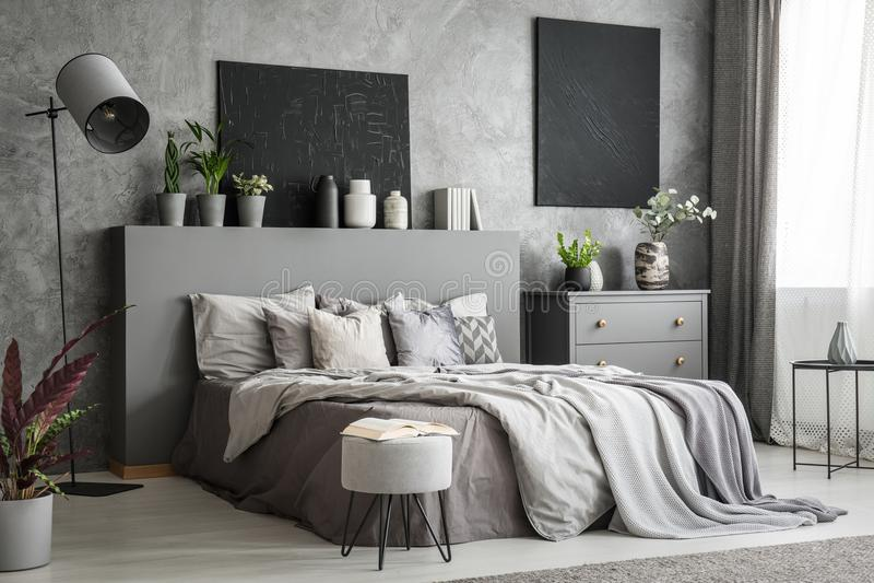 Stilvoller Schlafzimmerinnenraum im Grau mit einem großen Bett mit Bedsheets, stockfoto