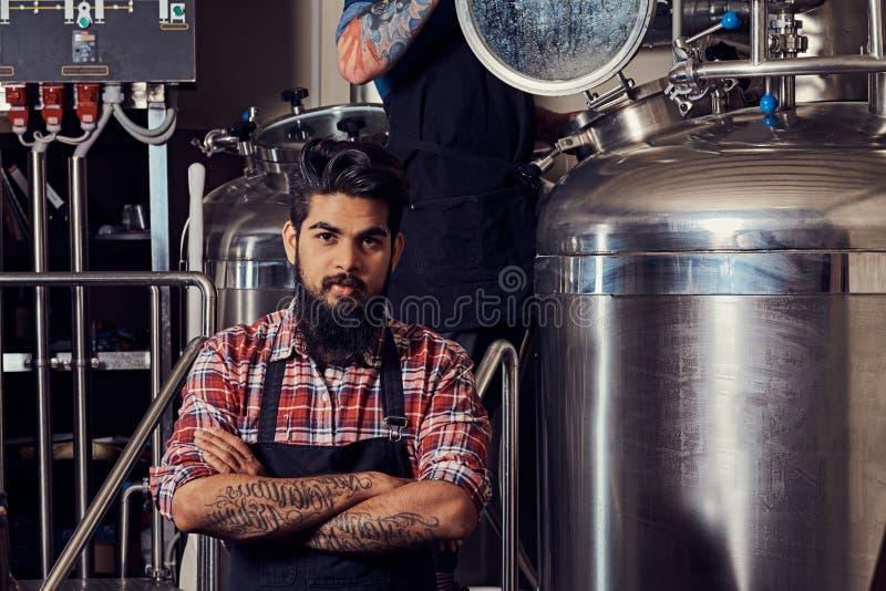 Stilvoller voller bärtiger indischer Mann in einem Vlieshemd und -schutzblech, die in einer Brauerei, werfend mit den gekreuzten  stockfotografie