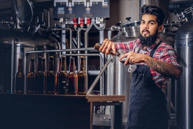 Stilvoller voller bärtiger indischer Mann in einem Vlieshemd und -schutzblech gießt Bier in einem Glas für Qualitätskontrolle und stockfotografie