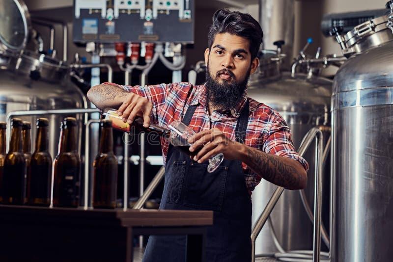 Stilvoller voller bärtiger indischer Mann in einem Vlieshemd und -schutzblech gießt Bier in einem Glas für Qualitätskontrolle und stockfotos