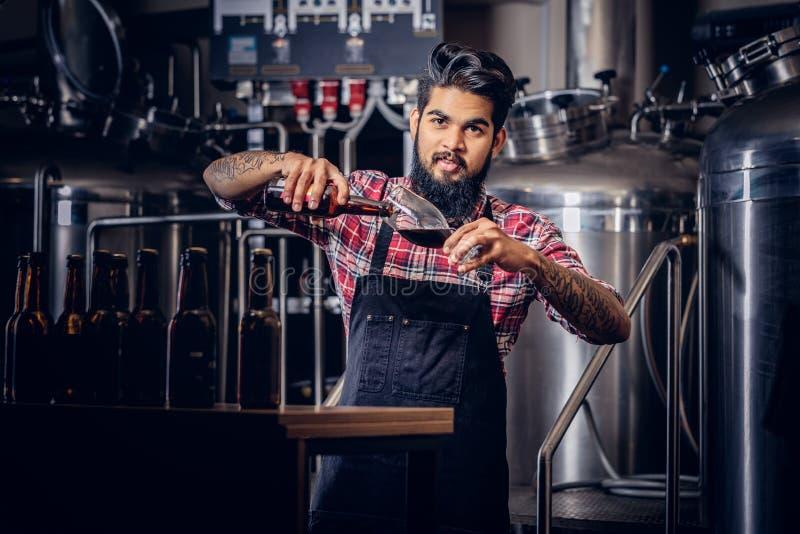 Stilvoller voller bärtiger indischer Mann in einem Vlieshemd und -schutzblech gießt Bier in einem Glas für Qualitätskontrolle und lizenzfreies stockbild