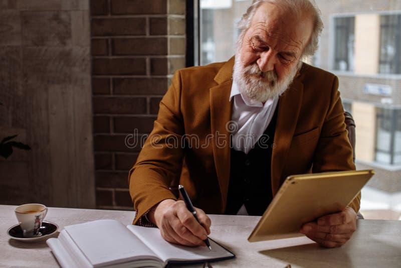 Stilvolles älteres Geschäftsmannstillstehen Trinkender Kaffee beim Arbeiten lizenzfreies stockbild