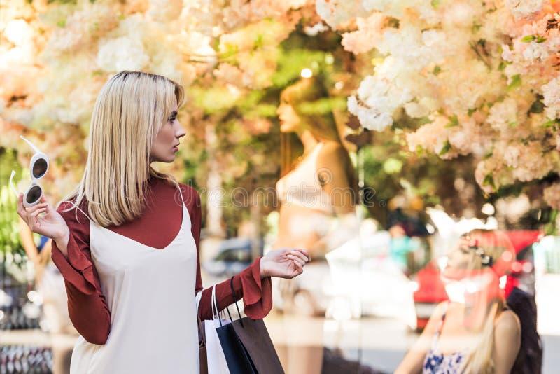 stilvolles blondes Mädchen, das Papiertüten hält und Attrappen betrachtet stockfoto