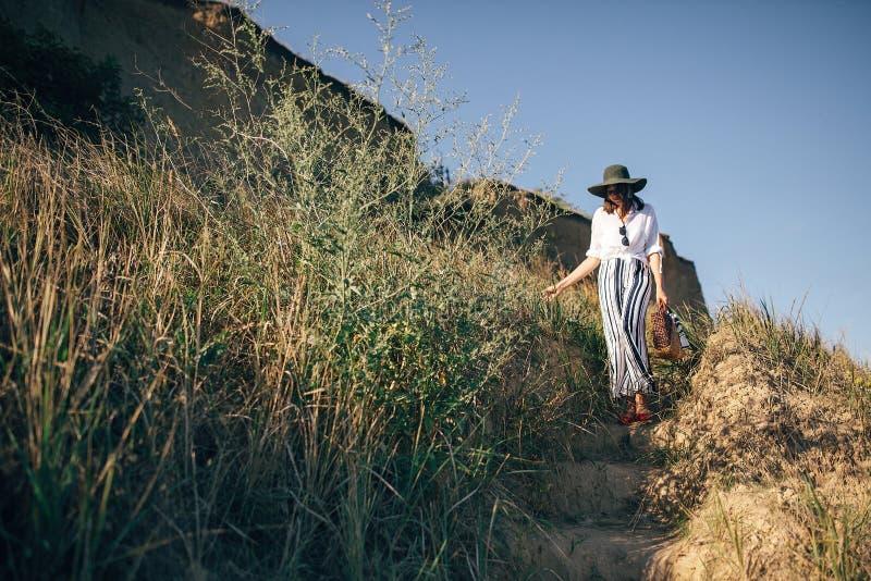 Stilvolles boho M?dchen im Hut gehend an der sandigen Klippe mit Gras nahe Meer, im sonnigen Licht Gl?ckliche junge Hippie-Frau,  lizenzfreie stockfotos