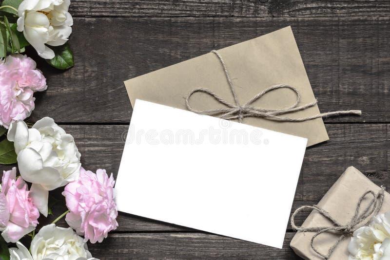 Stilvolles Brandingmodell, zum Ihrer Grafiken anzuzeigen Weinlesehochzeits-Grußkarte mit den rosa und weißen Rosen und Geschenkbo stockfotografie