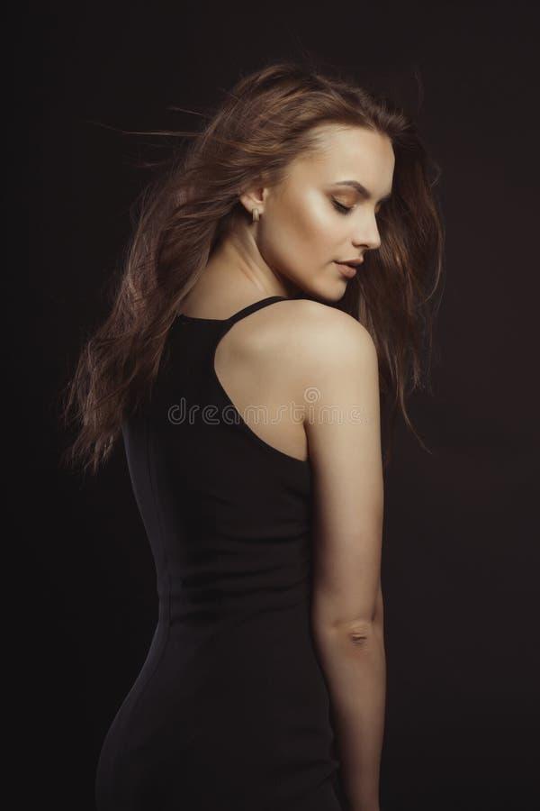 Stilvolles Brunettemodell im schwarzen Kleid mit dem gelockten Haar in der Bewegung stockfoto
