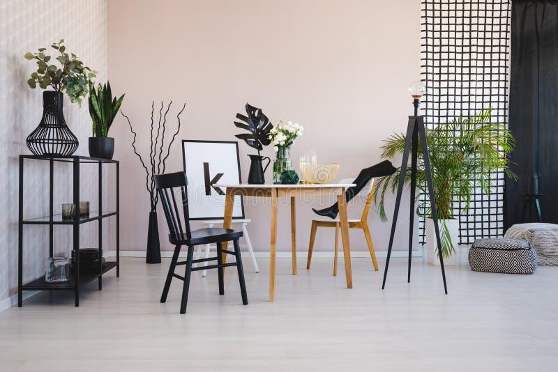 Stilvolles Esszimmer mit Rundtisch und bequeme Stühle, wirkliches Foto mit Kopienraum auf der leeren Wand lizenzfreies stockbild