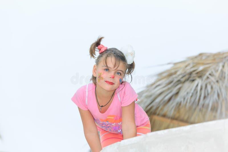 Stilvolles glückliches kleines Mädchen mit dem gemalten Gesicht, das neben dem Strandschirm auf weißem, bläulichem Hintergrund si stockfotografie