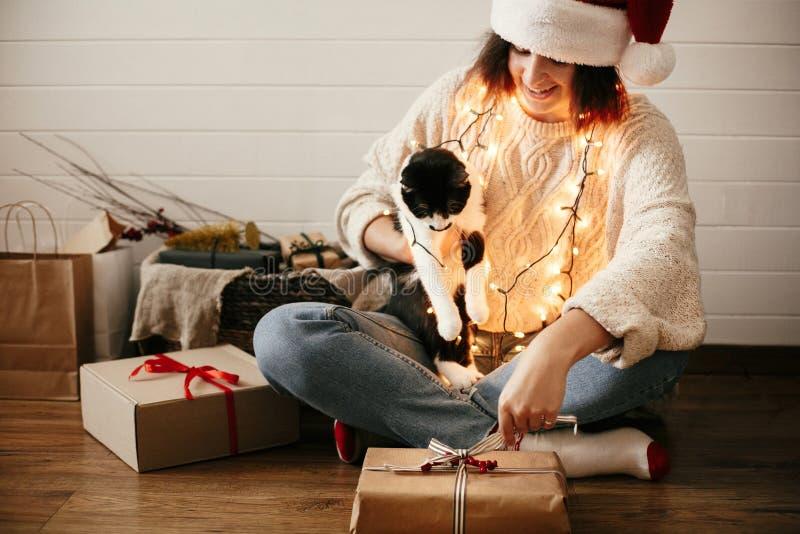 Stilvolles glückliches Mädchen in öffnender Geschenkbox Sankt-Hutes Weihnachtsmit netter Katze auf Hintergrund des modernen verzi stockfoto