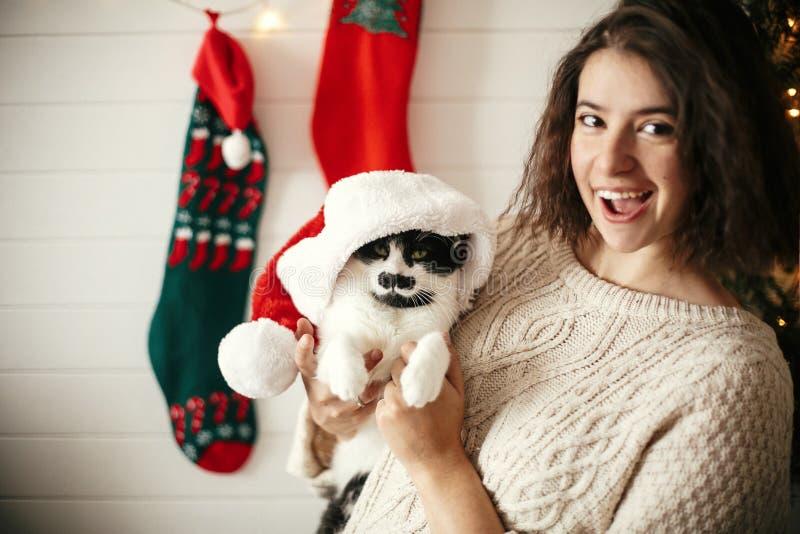 Stilvolles glückliches Mädchen, das mit netter Katze in Sankt-Hut im Hintergrund von Weihnachtsbaumlichtern und -strümpfen lächel lizenzfreie stockfotografie