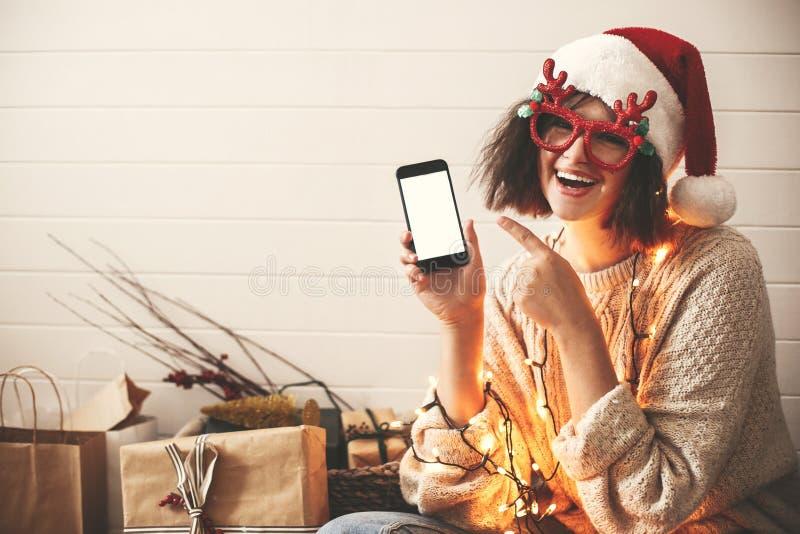 Stilvolles glückliches Mädchen in den festlichen Gläsern mit den Renhörnern, die Telefon leeren Schirm in den Weihnachtslichtern  stockfotos