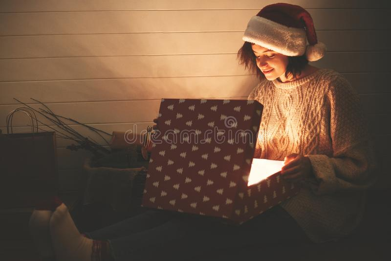 Stilvolles glückliches Mädchen in Sankt-Hut und in öffnender Geschenkbox der gemütlichen Strickjacke Weihnachtsmit magischem Lich lizenzfreie stockfotos