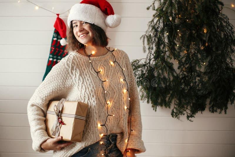 Stilvolles glückliches Mädchen in Sankt-Hut und in gemütlicher Strickjacke, die Weihnachtsgeschenkbox auf Hintergrund des moderne lizenzfreies stockfoto
