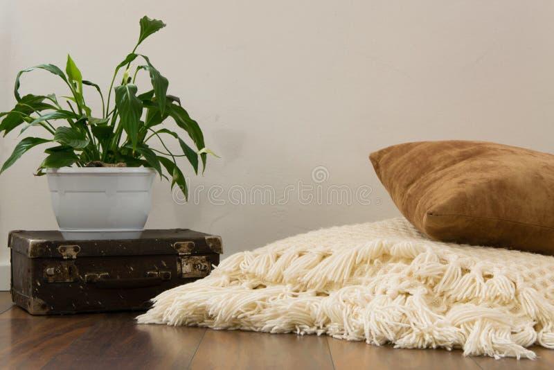 Stilvolles hell Teil des Wohnzimmers mit altem Weinlesekoffer, Topfpflanze und woolen handgemachter Decke auf Luxusbretterboden stockbild
