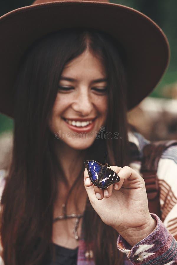 Stilvolles Hippie-Mädchen im Hut, der an Hand Schmetterling des purpurroten Kaisers in den Sommerbergen hält Reisender der jungen lizenzfreie stockfotografie