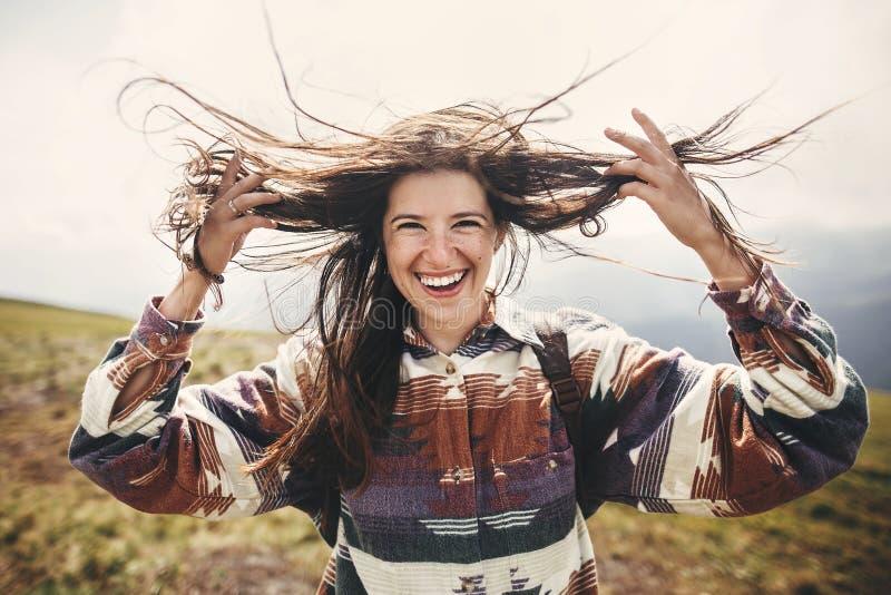 Stilvolles Hippie-Mädchen mit Rucksack und dem windigen Haar lächelnd auf Berge Porträt der glücklichen jungen entspannenden Frau lizenzfreie stockfotografie