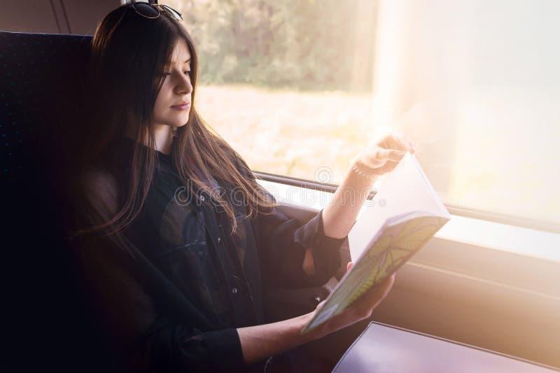Stilvolles Hippie-Mädchenlesebuch am Fensterlicht im Zug Trav stockbilder