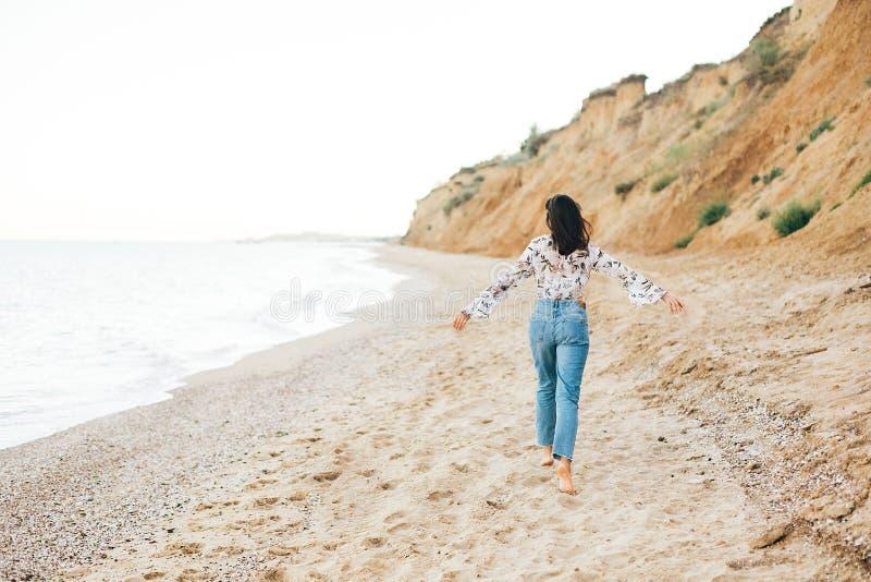 Stilvolles Hippie-M?dchen, das barfu? auf Strand in Meer, hintere Ansicht l?uft Gl?ckliche moderne boho Frau, die sich an an der  stockfotografie