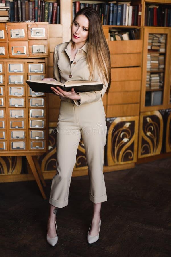 Stilvolles junges Mädchen in der Klage liest ein Buch an der Bibliothek lizenzfreie stockbilder