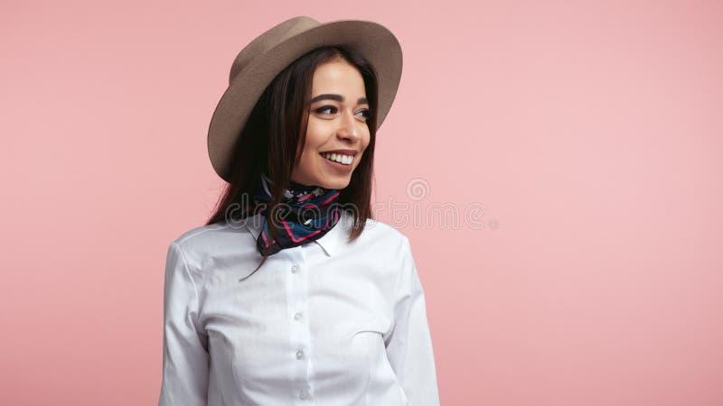 Stilvolles junges M?dchen, lacht gl?cklich, dr?ckt aufrichtige Gef?hle, tragendes wei?es Hemd und Hut, ?ber Rosa aus stockfoto
