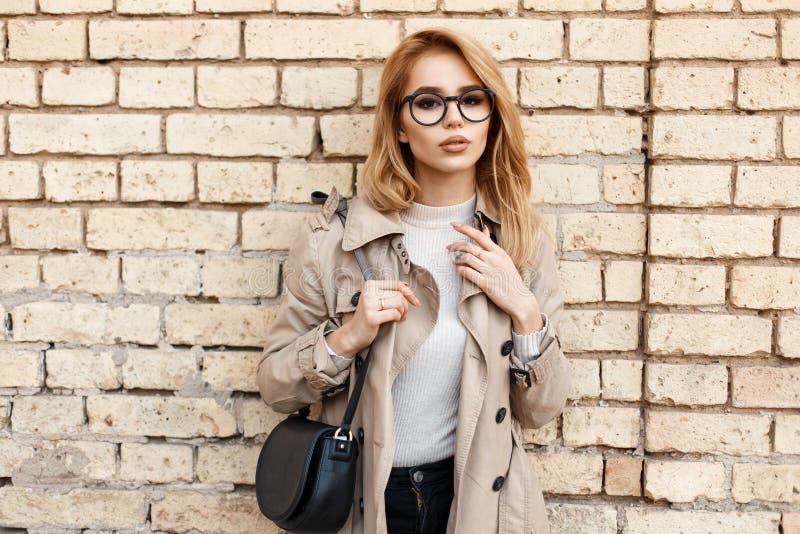 Stilvolles junges Mädchen mit Gläsern und Mantel mit einer Tasche lizenzfreie stockfotos