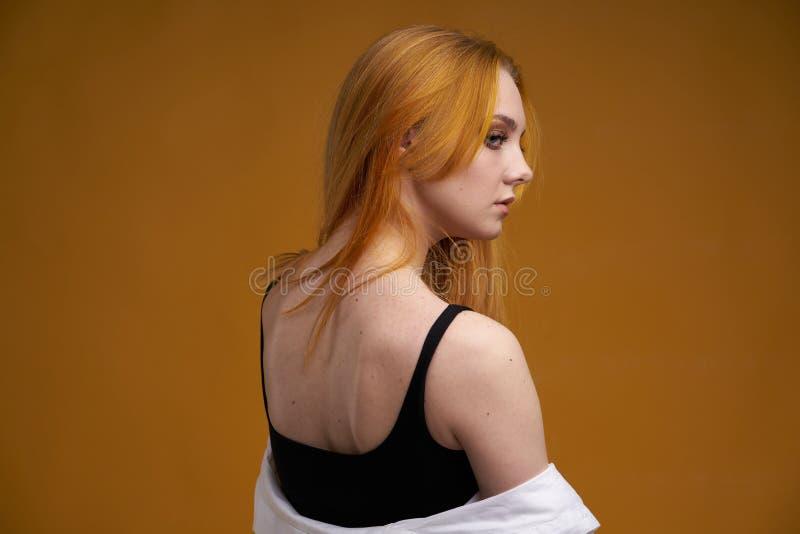 Stilvolles junges M?dchen mit dem gelockten Haar, nett l?chelnd und werfen, auf gelbem Hintergrund auf lizenzfreies stockbild