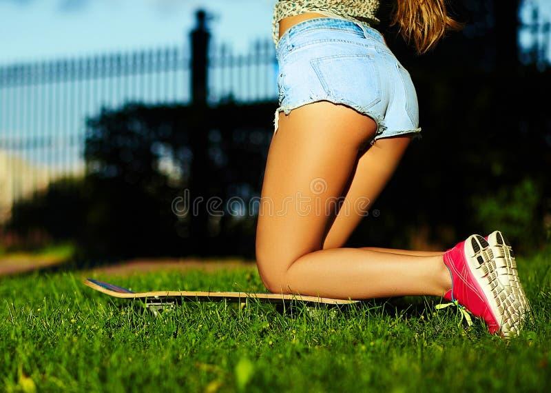 Stilvolles lächelndes Mädchen im hellen zufälligen Stoff in der kurzen Jeanshose draußen lizenzfreie stockbilder