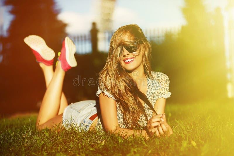 Stilvolles lächelndes Mädchen im hellen zufälligen Stoff in der kurzen Jeanshose draußen stockbilder