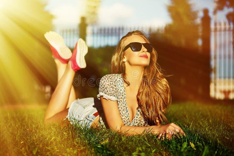 Stilvolles lächelndes Mädchen im hellen zufälligen Stoff in der kurzen Jeanshose draußen stockfoto