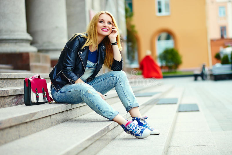 Stilvolles lächelndes Mädchen im zufälligen Stoff im Stadtpark stockfotos