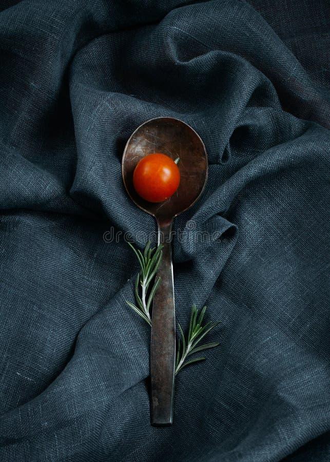 Stilvolles Lebensmittel Silberner Löffel mit Rosmarin- und Kirschtomate stockbilder