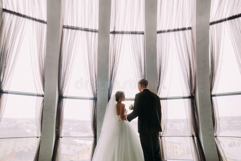 Stilvolles Luxusbraut- und Bräutigamhändchenhalten am herrlichen Fenster auf dem Hintergrund des Innenraums im modernen Gebäude lizenzfreies stockfoto