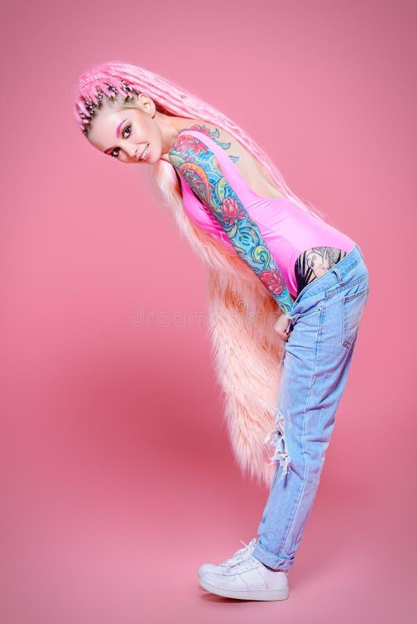 Stilvolles Mädchen über Rosa stockbilder