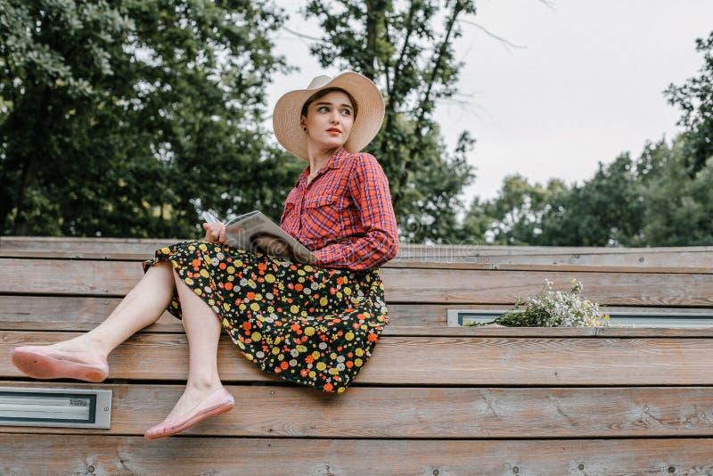 Stilvolles Mädchen, das ein Buch liest Eine Schönheit mit einem Hut, der auf Treppe eines Baums sitzt Ein Student liest ein Buch stockbilder