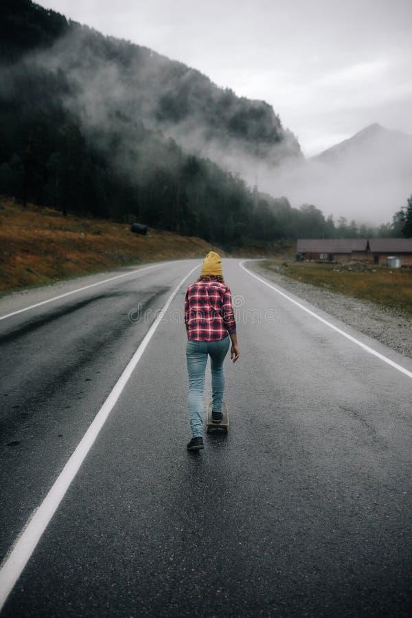 Stilvolles Mädchen in einer Kappe auf einem Stoß an der Landstraße in den Bergen mit einem Skateboard lizenzfreies stockbild