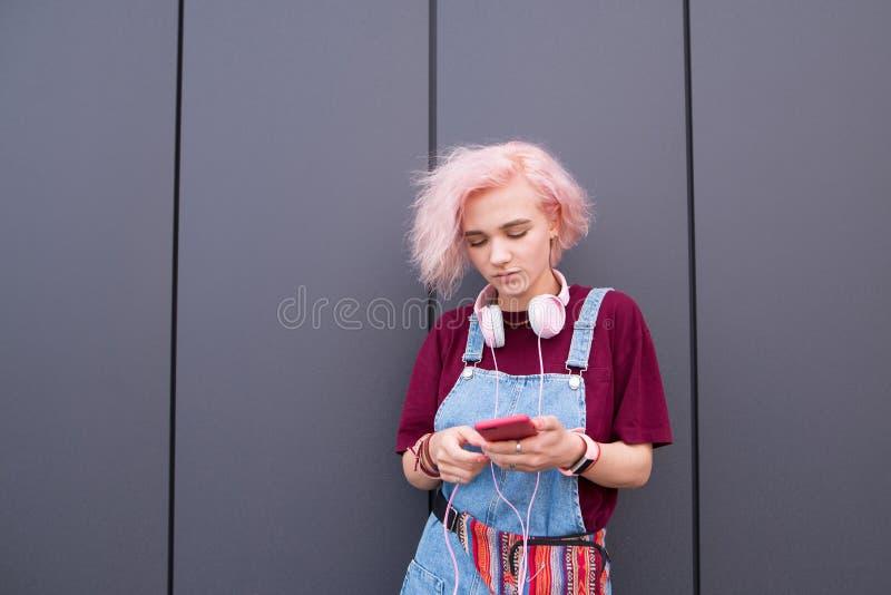Stilvolles Mädchen mit dem farbigen Haar, den rosa Kopfhörern und einem Smartphone in ihren Händen auf einem dunklen Hintergrund stockbild