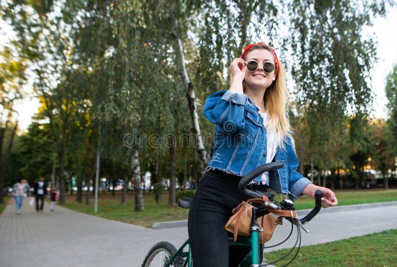 Stilvolles Mädchen mit einer Fahrradstellung im weg schauenden und lächelnden Park Frau fährt Fahrrad im Park stockfotos
