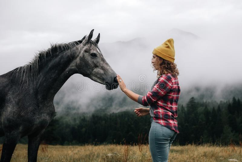 Stilvolles Mädchen mit Kappenblick und das Pferd über Bergen im Nebel streicheln stockfotos