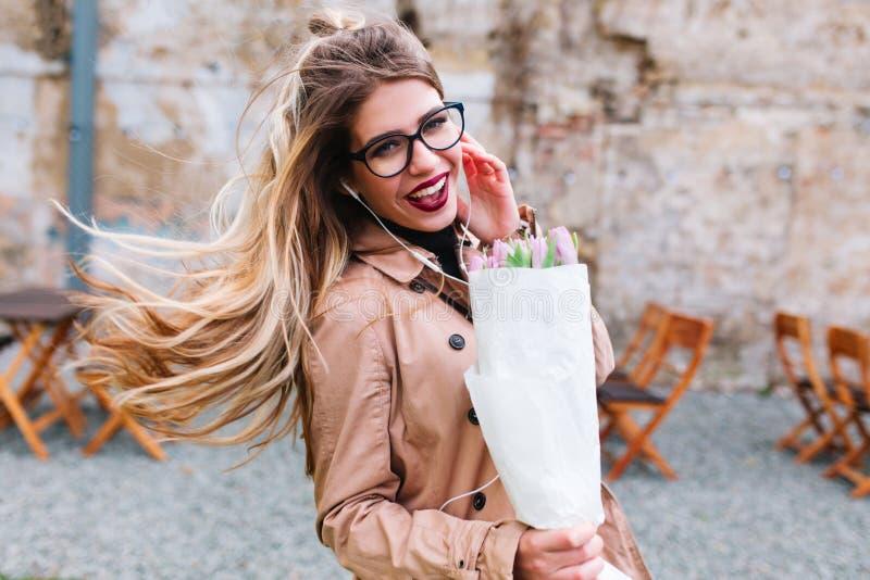 Stilvolles Mädchen mit tragenden Gläsern der hübschen Frisur täuscht herum und das Lachen, das Tulpenblumenstrauß trägt Entz?cken lizenzfreie stockfotos