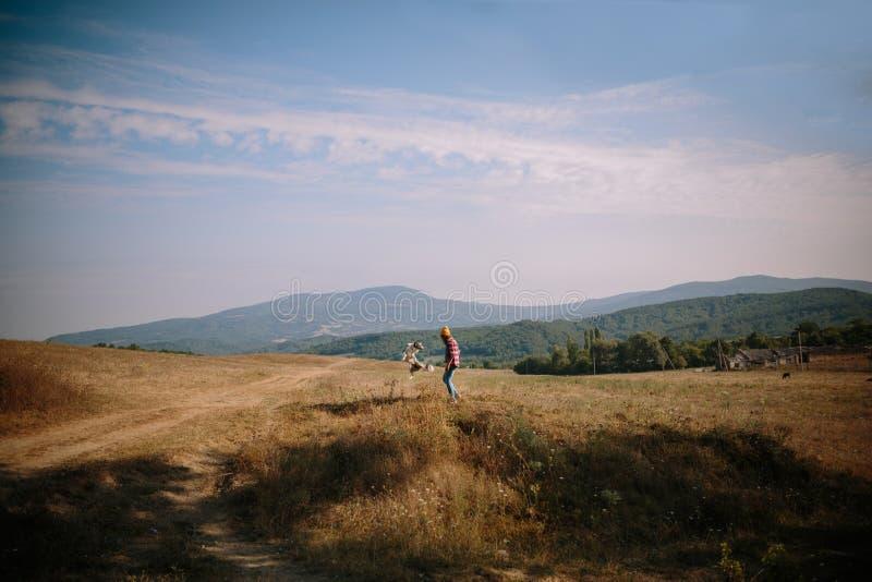 Stilvolles Mädchen und ein Hund zum Feld auf einer Sitzung mit Abenteuern gehen lizenzfreie stockbilder