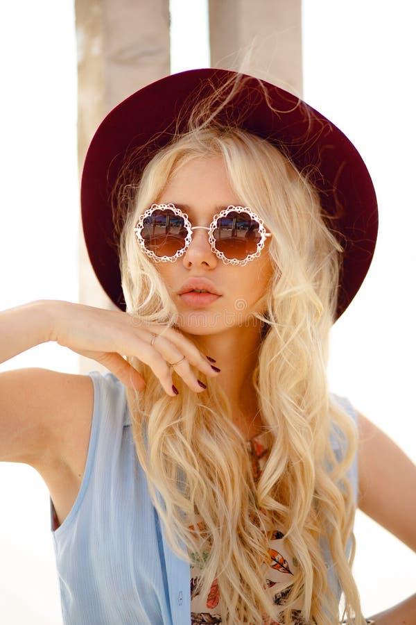Stilvolles Mädchen wirft auf dem Sonnenscheinplatz auf und trägt in einem Hut und in einer Rundenblumensonnenbrille, das sinnlich stockfotos