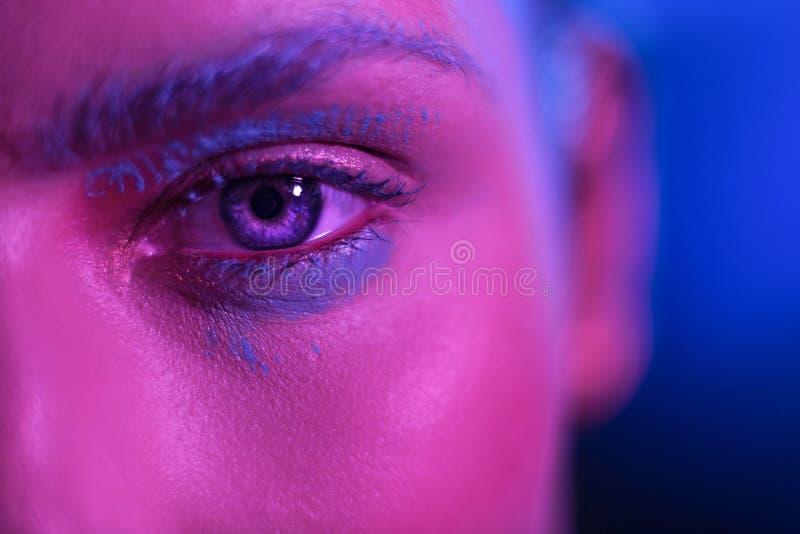 Stilvolles Mädchenmodell des hellen Makes-up mit blauen Augen auf einem blauen Hintergrund lizenzfreie stockfotos