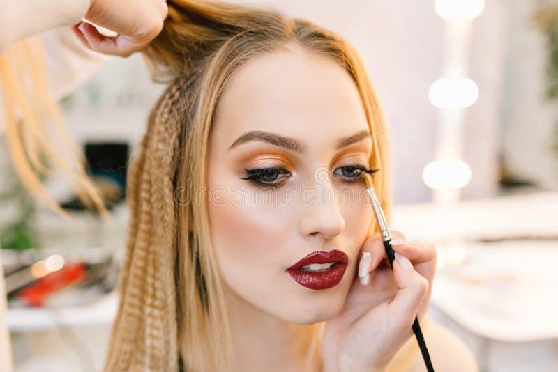 Stilvolles Nahaufnahmeportr?t der herrlichen jungen Frau im Friseursalon, der zur Partei sich vorbereitet Herstellung von Frisur, stockfotografie