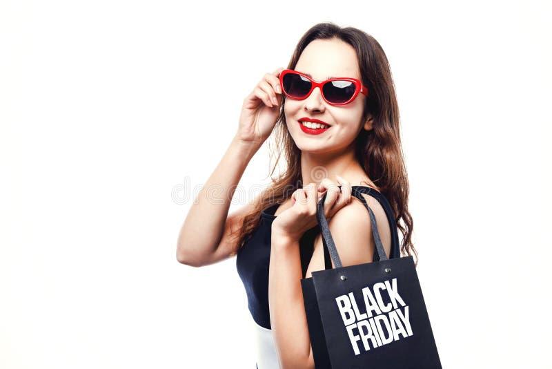Stilvolles nettes Mädchen, das Black Friday-Einkaufstasche hält lizenzfreie stockfotos