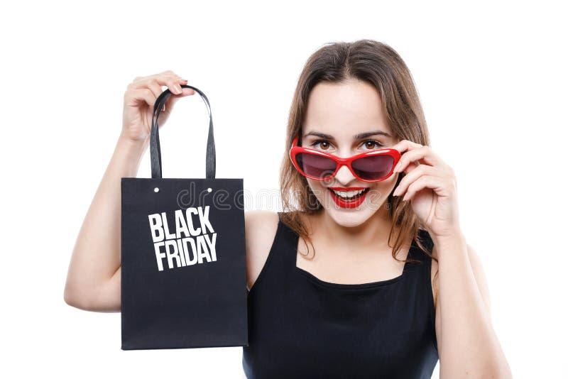 Stilvolles nettes Mädchen, das Black Friday-Einkaufstasche zeigt stockfotografie