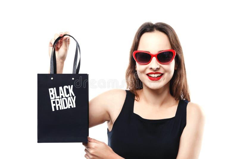 Stilvolles nettes Mädchen, das Black Friday-Einkaufstasche zeigt stockbilder