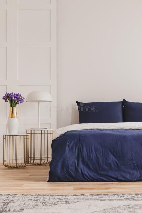 Stilvolles nightstand mit industrieller Lampe und modischem Nachttisch mit Blumen im Vase nahe bei einfachem Marineblaubett stockfotografie