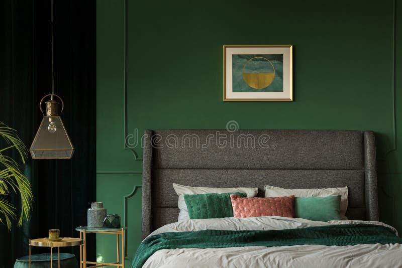 Stilvolles Plakat über bequemem Königgrößenbett mit Kopfende im dunkelgrünen Schlafzimmer stockbilder