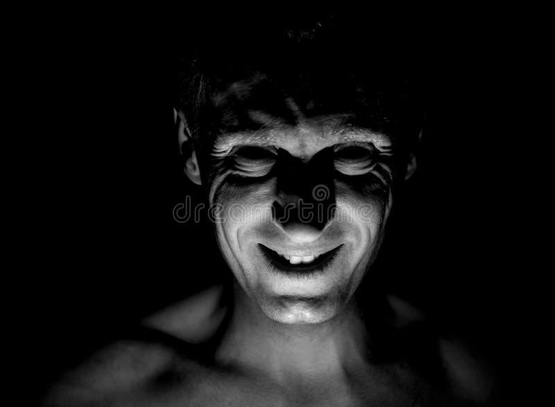 Stilvolles Porträt des erwachsenen kaukasischen Mannes Er lächelt wie Wahnsinnige und scheint wie Wahnsinnige oder verrückt stockfotos